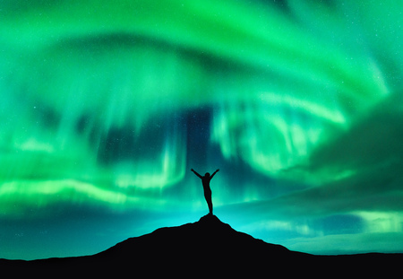 Aurora borealis and silhouette of a woman with raised up arms on the mountain peak. Lofoten islands, Norway. Aurora and happy girl. Starry sky and polar lights. Night landscape with aurora and people Imagens