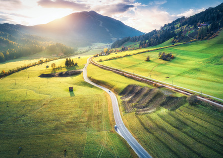 Aerial view of the road in mountain valley at sunset in summer in Dolomites, Italy. Top view of asphalt roadway, railroad, hills with green meadows, blue sky, trees, buildings. Highway and fields