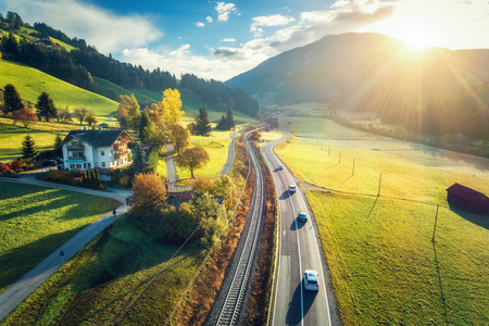 Aerial view of the road in mountain valley at sunset in spring in Dolomites, Italy. Top view of cars on asphalt roadway, house, railroad, hills with green meadows, blue sky, trees, buildings. Highway Фото со стока