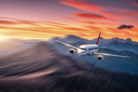 Airplane in motion. Aircraft with motion blur effect is flying over hills and mountains at sunset. Passenger airplane, blurred clouds. Passenger aircraft in motion. Business travel. Commercial.Concept