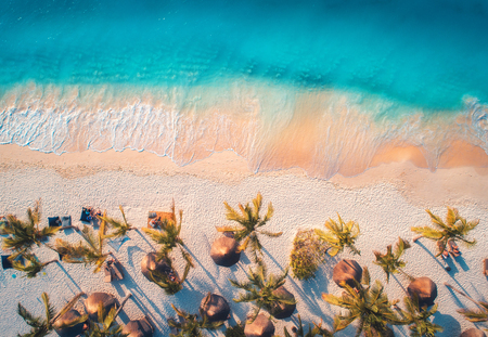 Aerial view of umbrellas, palms on the sandy beach of blue sea at sunset. Summer travel in Zanzibar, Africa. Tropical landscape with palm trees, parasols, people, sand, waves. Top view from the air