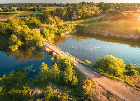 Aerial view of beautiful countryside at sunset. Summer rural landscape with old bridge, dirt road, green trees, hills, people in boat on the river. Top view of country road, forest, blue water. Nature