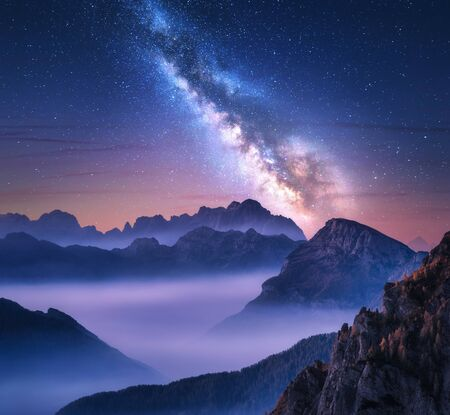 Milky Way over mountains in fog at night in summer. Landscape with alpine mountain valley, purple low clouds, colorful starry sky with milky way. Passo Giau, Dolomites, Italy. Space. Beautiful nature