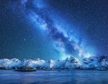 Vía Láctea brillante sobre las montañas cubiertas de nieve y el mar por la noche en invierno en Noruega. Paisaje con rocas nevadas, cielo estrellado, reflejo en el agua, fiordo. Islas Lofoten. Espacio. Hermosa vía láctea Foto de archivo