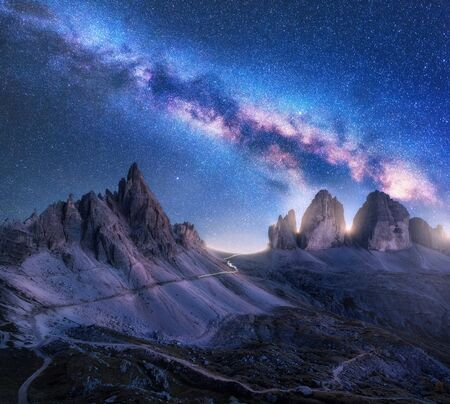 Bright Milky Way over mountains at starry night in summer. Amazing landscape with alpine mountains, blue sky with milky way and stars, high rocks. Tre Cime in Dolomites, Italy. Space. Beautiful nature