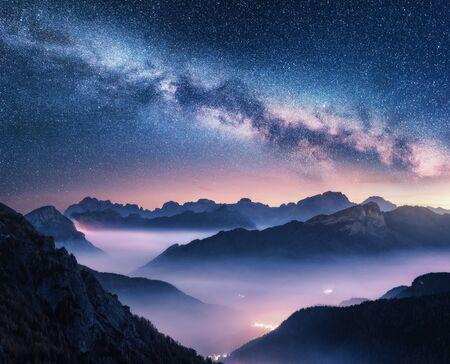 Milchstraße über Bergen im Nebel nachts im Sommer. Landschaft mit nebligen Alpental, lila Wolken, bunter Sternenhimmel mit Milchstraße, Stadtbeleuchtung. Dolomiten, Italien. Platz