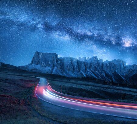 Via Lattea sulla strada di montagna di notte in estate. Fari auto sfocati sulla strada tortuosa. Paesaggio colorato con cielo con stelle e via lattea blu, sentieri di luce, rocce, alberi e autostrada. Spazio Archivio Fotografico