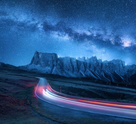 Voie lactée sur route de montagne la nuit en été. Phares de voiture flous sur route sinueuse. Paysage coloré avec ciel avec étoiles et voie lactée bleue, sentiers lumineux, rochers, arbres et autoroute. Espacer Banque d'images