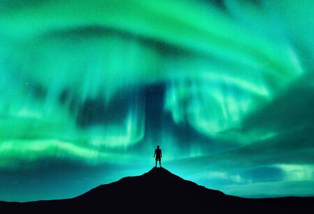 Aurora borealis und Silhouette eines Mannes auf dem Berggipfel. Lofoten-Inseln, Norwegen. Schöne Aurora und Mann. Alleinreisender. Himmel mit Sternen und Polarlichtern. Nachtlandschaft mit Nordlichtern