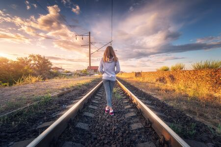 Standing young woman on the railroad at sunset in summer. Slim girl on the railway station. Rural industrial landscape with railroad, sky with colorful clouds. Railway platform. Transportation. Travel