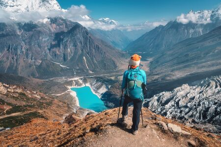 Standing woman with backpack on the mountain peak. Beautiful mountains in clouds, lake with azure water at sunset. Landscape with alone girl, snowy rocks, sky, glacier in Nepal. Travel. Trekking