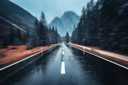 Road in the autumn forest in rain with motion blur effect. Perfect asphalt mountain road in overcast rainy day with blurred background. Roadway in motion. Transportation. Empty highway. Fast driving