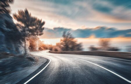 Mountain road at sunset with motion blur effect. Asphalt road and blurred background with rocks, blue sky with sun and clouds in summer. Fast driving. Beautiful highway in motion. Transportation