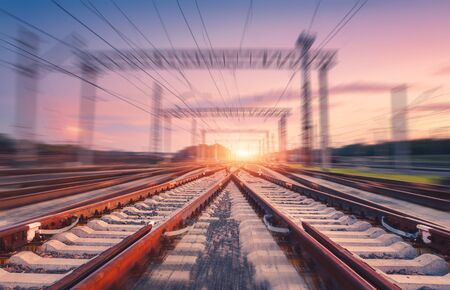 Railroad and pink sky with motion blur effect at sunset. Industrial landscape with railway station, light and blurred background at twilight. Railway platform in move. Transportation. Speed motion Stock fotó
