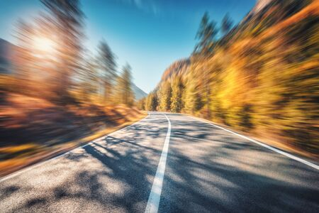 Mountain road in autumn forest at sunset with motion blur effect. Asphalt road and blurred background with orange trees, blue sky with sun in fall. Fast driving. Beautiful highway. Transportation