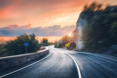 Mountain road at sunset with motion blur effect. Asphalt road and blurred background with rocks, orange sunny sky with clouds in summer. Fast driving. Beautiful highway in motion. Transportation
