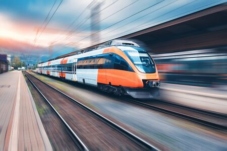 Treno arancione ad alta velocità in movimento sulla stazione ferroviaria al tramonto. Moderno treno passeggeri interurbano con effetto motion blur sulla piattaforma ferroviaria. Industriale. Ferrovia in Europa. Trasporto