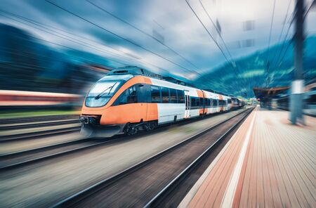 Train orange à grande vitesse en mouvement sur la gare au coucher du soleil. Train de voyageurs interurbain moderne avec effet de flou de mouvement sur la plate-forme ferroviaire. Industriel. Chemin de fer en Europe. Transport