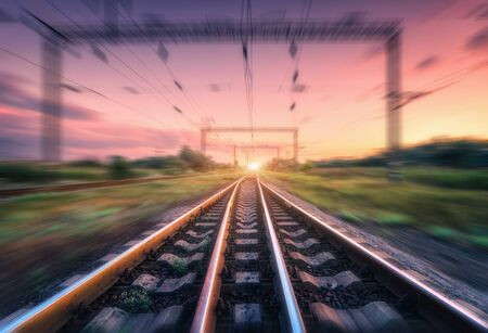 Railroad and beautiful sky at sunset with motion blur effect in summer. Industrial landscape with railway station and blurred background with colorful sky. Railway platform in speed motion. Sleepers