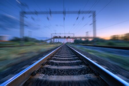Ferrovia e cielo blu al tramonto con nuvole con effetto motion blur. Paesaggio industriale con stazione ferroviaria e sfondo sfocato al crepuscolo. Piattaforma ferroviaria in movimento. Trasporto. Velocità di movimento Archivio Fotografico