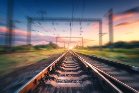 Railroad and colorful blue sky with clouds at sunset with motion blur effect in summer. Industrial landscape with railway station and blurred background. Railway platform in speed motion. Concept