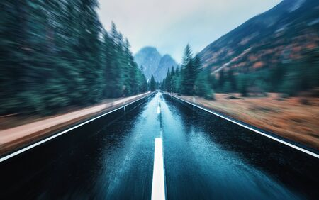 Road in the autumn forest in rain with motion blur effect. Perfect asphalt mountain road in overcast rainy day with blurred background. Roadway in motion. Transportation. Empty highway. Fast driving Stock fotó - 129814176