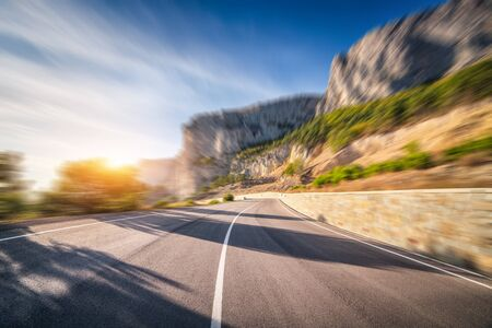 Mountain road at sunrise with motion blur effect. Asphalt road and blurred background with rocks, blue sky with sun and clouds in summer. Fast driving. Beautiful highway in motion. Transportation
