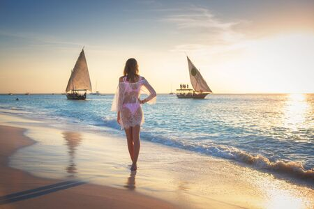 Beautiful young woman is standing in sea with waves on sandy beach against sailboats at sunset. Summer travel. Tropical landscape with slim girl in white lace dress on the seashore, boats and yachts