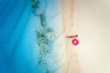 Aerial view of the beautiful young lying woman with pink donut swim ring on white sandy beach near blue sea with waves at sunset. Tropical summer holiday. Top view of slim girl, clear water. Leisure