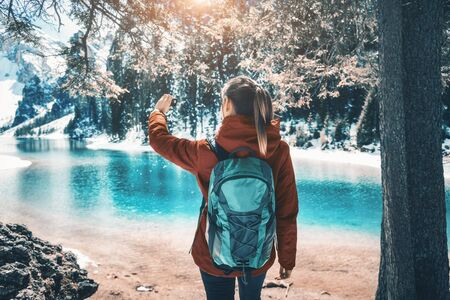 Beautiful young woman with backpack taking a selfie on the lake at sunset in autumn. Landscape with sporty girl is making photo, green trees, azure water in Dolomites, Italy. Travel in fall