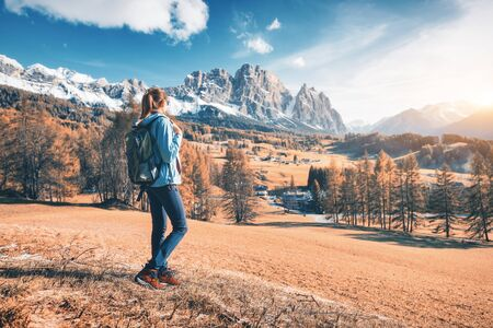 Beautiful young woman with backpack is standing on the hill against mountains at sunset in autumn. Landscape with sporty girl, rocks with snowy peaks, meadow, orange trees, blue sky in Italy. Travel