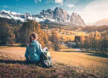 Beautiful young woman with backpack is sitting on the hill against mountains at sunset. Colorful autumn landscape with girl, grass, orange trees and snowy rocks. Travel in Dolomites, Italy in fall