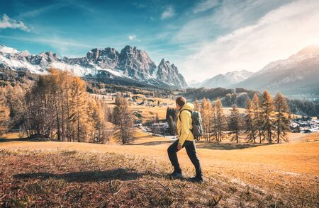 Young man in yellow jacket with backpack is walking on the meadow against the mountains at sunset in autumn. Landscape with sporty guy, snowy rocks, orange trees, blue sky. Travel in Italy in fall