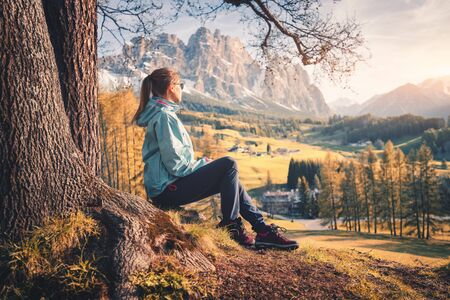 Beautiful young woman in blue jacket is sitting on the hill under the tree at sunset. Colorful autumn landscape with sporty girl, meadows, orange trees and mountains. Travel in Italy in fall. Nature Фото со стока
