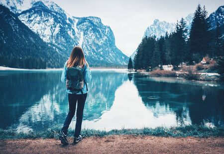 Young woman with backpack is standing on the coast of mountain lake at cloudy day in autumn. Travel in Italy in fall. Landscape with slim girl, reflection in water, snowy rocks, trees. Vintage toning