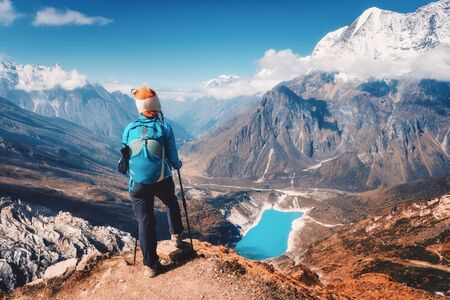 Woman with backpack on the mountain peak in autumn. Beautiful mountains in clouds, lake with azure water at sunset. Landscape with alone girl, snowy rocks, sky, glacier in Nepal. Travel in fall