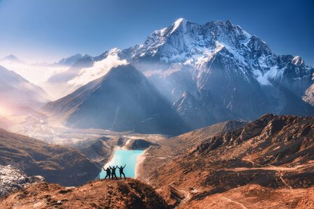 Happy people with raised up arms on the mountain peak, beautiful lake, snowy mountain at sunrise in autumn. Landscape with man and woman, rocks in clouds, ky with sunrays. Travel in Nepal in fall