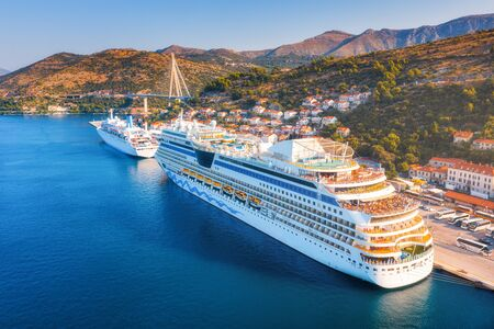 Cruise ship at harbor. Aerial view of beautiful large ships and boats at sunrise. Landscape with boats in harbour, city, mountains, blue sea. Top view of yacht. Luxury cruise. Floating liner in port