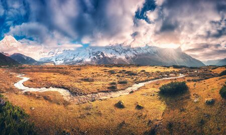 Panoramic landscape with mountains with snow covered peaks in purple clouds, sun, small river, orange grass, blue sky at sunrise. Colorful scenery with meadows, creek, snowy rocks. Autumn in Nepal 写真素材