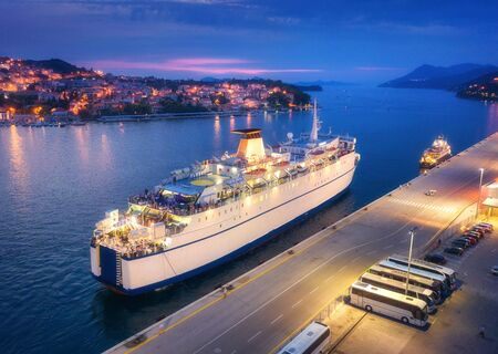 Aerial view of cruise ship at harbor at night. Landscape with ships and boats in harbour, city illumination, buildings, mountains, blue sea at sunset. Top view. Luxury cruise. Floating liner in port