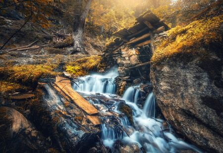 Stony well in colorful forest with little waterfall in mountain river at sunset in autumn. Landscape with stones in water, building, orange trees, waterfall and vibrant foliage in fall. Nature