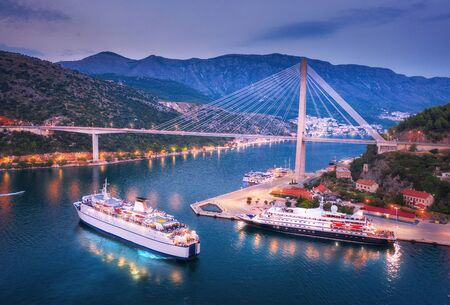 Aerial view of cruise ship at harbor and beautiful bridge at night. Landscape with ships and boats in harbour, city illumination, road, mountains, blue sea at sunset. Top view. Floating liner in port 版權商用圖片