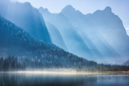 Majestic mountains in bright sunbeams and foggy lake at sunny morning in autumn. Fall in Dolomites, Italy. Landscape with fog over water, high rocks and hills, forest and sunlight at sunrise. Nature