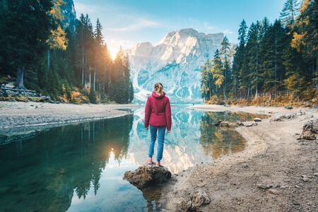 Woman is standing on the stone on Braies lake at sunrise in autumn. Dolomites, Italy. Landscape with girl, mountain, lake, beautiful reflection in water, trees, sky with sun. Forest in fall. Travel