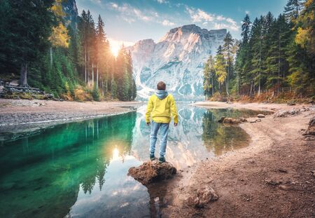 Man is standing on the stone on Braies lake at sunrise in autumn. Dolomites, Italy. Landscape with guy, mountains, beautiful reflection in water, colorful trees, blue sky with sun. Forest in fall