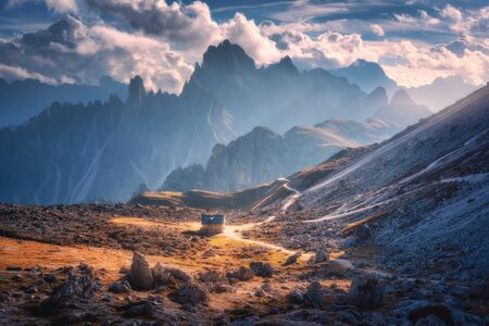Small house in beautiful mountain valley, orange grass, stones, blue sky with clouds at sunset in autumn. Colorful landscape with building, mountains. Tre Cime park in Dolomites, Italy. Alps in fall Banco de Imagens
