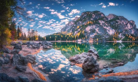 Beautiful Braies lake at sunrise in autumn in Dolomites, Italy. Landscape with mountains, blue sky with clouds, water with reflection, stones, trees with colorful leaves. Lake in fall. Panorama