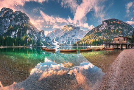 Amazing Braies lake at sunrise in autumn in Dolomites, Italy. Landscape with mountains, sky with clouds, boats, water with reflection, trees with colorful leaves. Lake in fall. Italian alps. Panorama