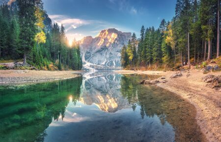 Amazing Braies lake at sunrise in autumn in Dolomites, Italy. Landscape with mountains, blue sky with clouds, water with reflection, trees with colorful leaves. Lake in fall. Italian alps. Panorama