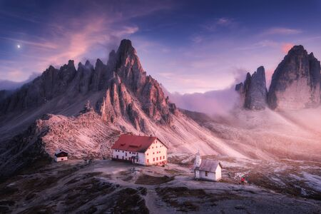 Mountains with beautiful house and church at sunset in autumn. Landscape with buildings, high rocks, purple sky with moon and clouds, sunlight. Mountains in fog. Tre Cime park in Dolomites, Italy Banco de Imagens